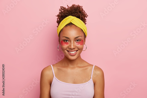Canvas-taulu Portrait of good looking dark skinned young African American woman wears cosmetic collagen patches, wears headband and casual t shirt, isolated over pink background
