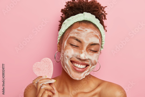 Fotografía  Beautiful optimistic Afro American woman cleanses face with foam, refreshes skin