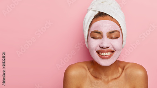 Cuadros en Lienzo  Close up portrait of young female model applies homemade facial clay mask, has white towel wrapped around head, keeps eyes shut, smiles happily, models against pink background