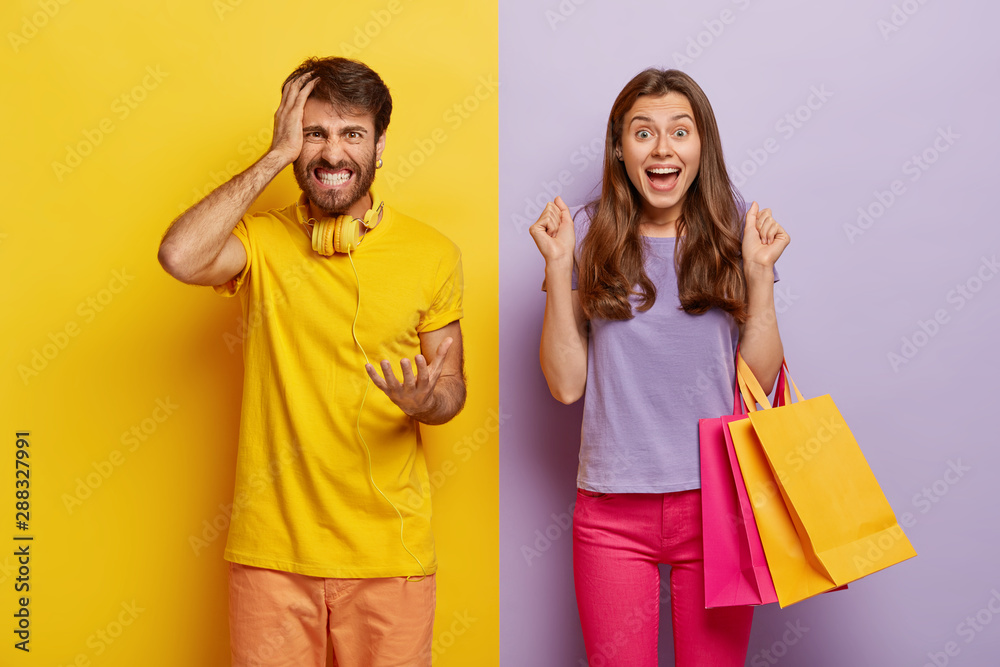 Fototapeta Cheerful female carries colorful shopping bags, rejoices new purchase, clenches fists with joy, annoyed husband feels angry with wife shopaholic, gestures with irritation, poses against colorful wall