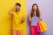 canvas print picture - Cheerful female carries colorful shopping bags, rejoices new purchase, clenches fists with joy, annoyed husband feels angry with wife shopaholic, gestures with irritation, poses against colorful wall