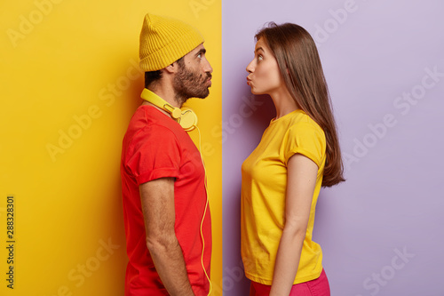 Obraz Woman and man stand in profile, keep lips folded, stare at each other, going to kiss, wear casual t shirts, headphones around neck, make grimace, pose indoor, have fun. Facial expressions concept - fototapety do salonu