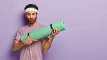 Studio Shot Of Serious Motivated Man With Thick Bristle, Holds Rollled Up Kareamt, Makes Grimace, Ready For Yoga Training, Wears Casual Clothes, Isolated Over Purple Wall With Empty Space For Advert
