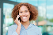 Young cheerful businesswoman with curly brown hair talking on smartphone