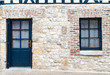 canvas print picture - typical stone house facade in Normandy in France with blue doors and windows for contrast