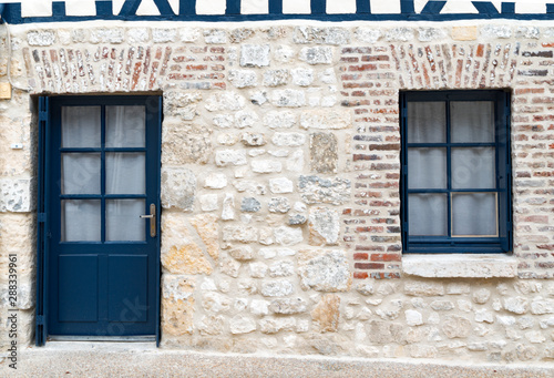 Fotografía  typical stone house facade in Normandy in France with blue doors and windows for