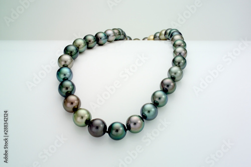 Fotografía  A necklace of a single strand of Tahitian pearls is laid over a curve white surface