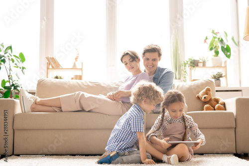 Happy young parents on couch looknig at their children on the floor Poster Mural XXL