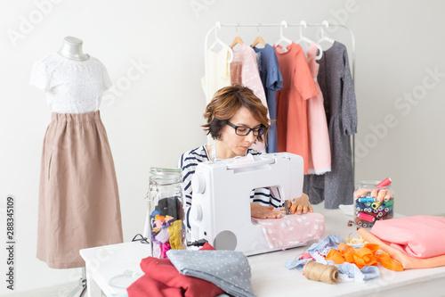clothing designer, seamstress, people concept - clothing designer working in her Lerretsbilde