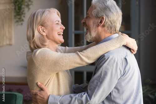 Happy senior couple relax dancing at home together Poster Mural XXL