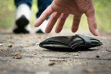 Wallet Dropped From A Woman Pocket And A Male Hand Picking Up It From A Ground.