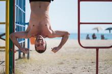 Man Hanging Upside Down At Kids Playground