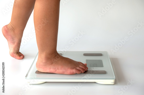 Photo side view close-up of kid feet on digital body fat analyzer scales on white background