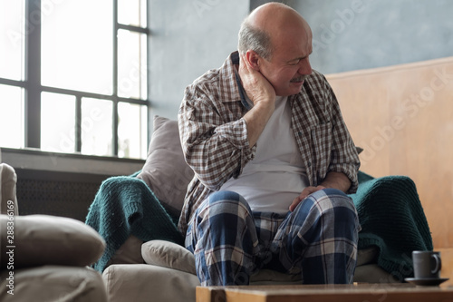 Photographie Senior hispanic man is having neck pain because of osteochondrosis
