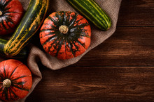 Flat Lay Photo Orange Pumpkins And Green Zucchini On Sacks Of Jute. Old Wooden Background