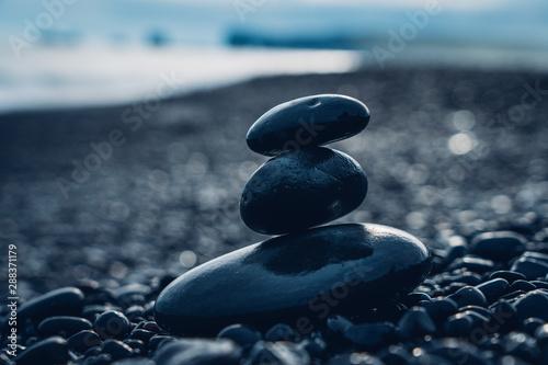 Photo sur Aluminium Zen pierres a sable Pierres sur plage de sable noir
