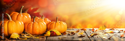 Obraz Banner Of Thanksgiving Pumpkins And Leaves On Rustic Wooden Table With Sunlight And Bokeh On Orange Background - Thanksgiving / Harvest Concept - fototapety do salonu