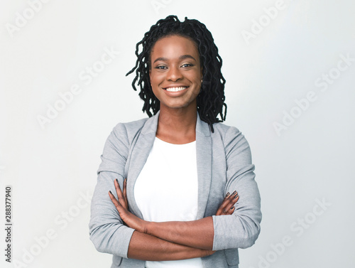fototapeta na drzwi i meble Young Black Businesswoman Smiling At Camera Crossing Hands, Studio Shot