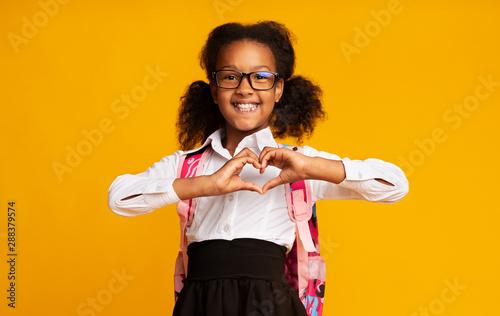 African American Schoolgirl Showing Heart Gesture With Hands In Studio Canvas Print