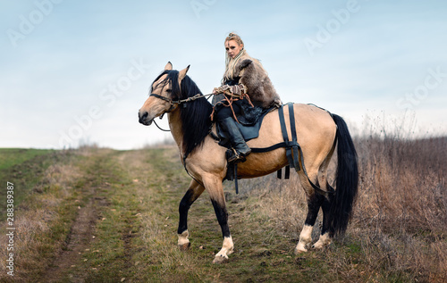 Warrior viking blonde female riding a horse - Medieval movie scene Canvas Print