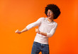 Leinwanddruck Bild - Cheerful bushy black man dancing on orange background