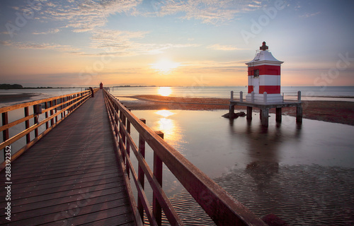 Obraz Italy beach - Lignano Sabbiadoro Lighthouse with beach at sunrise - fototapety do salonu