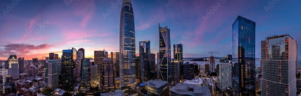 Fototapeta Twilight with a pink and blue sunset over San Francisco skyline with Salesforce Tower in the middle and Salesforce park at the bottom