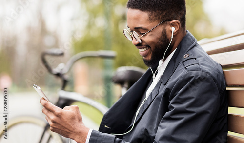 Young businessman sitting on bench and listening music Fototapete