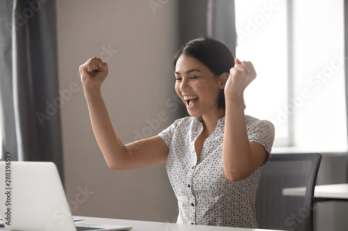 Fotografía  Excited young asian business woman celebrating successful financial project results