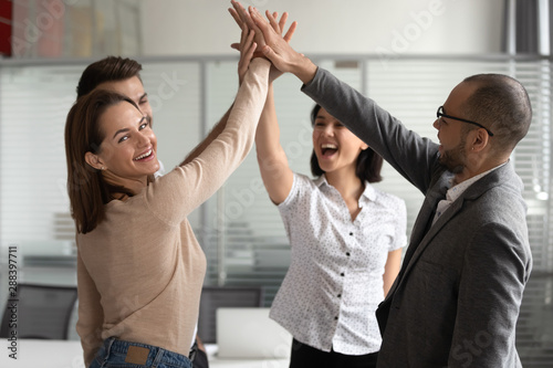 Cuadros en Lienzo Excited young female team leader giving high five to colleagues.
