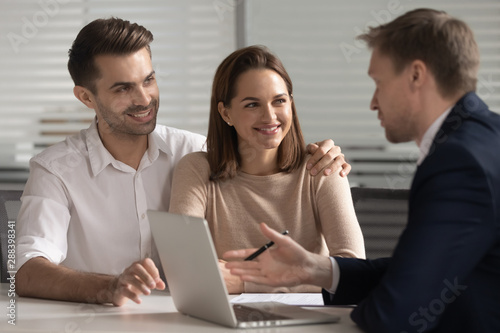 Smiling couple consulting with financial advisor or real estate agent.