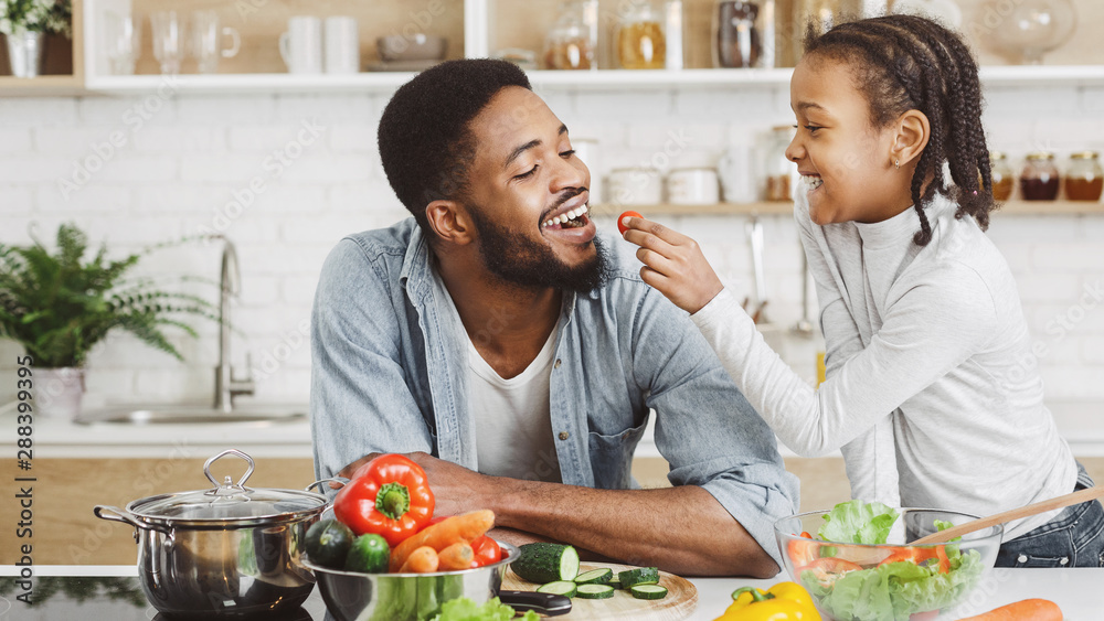 Fototapeta Cute african girl giving her dad cherry tomato while cooking