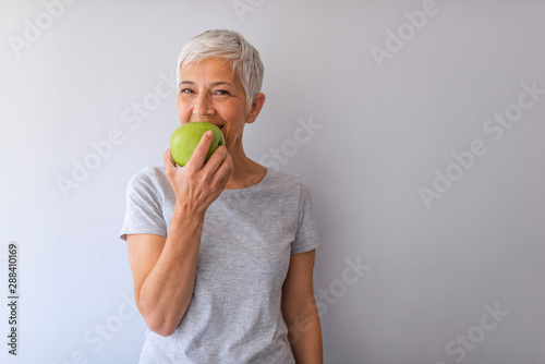 Portrait of happy mature woman holding granny smith apple at home Fototapete