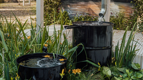 Photo Rain water flows from a drainpipe to the metal barrel in garden in summer close