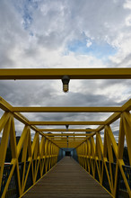 Portrait View Of Blue And Yellow Pedestrian Bridge With Lights And Blue Sky Background