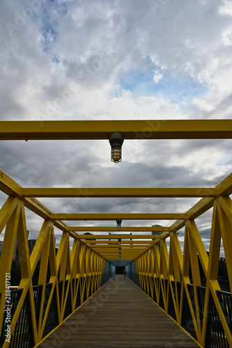 Vászonkép  Portrait View of Blue and Yellow Pedestrian Bridge with Lights and Blue Sky Back