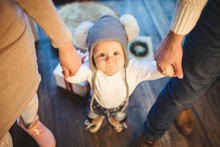 Funny Little Baby Boy 1 Year Old Learning Walk Home In Winter In A Decorated New Year House. Young Family Dad And Mom Hold By The Hands Of His Son In The Loft Interior Wooden Floor Near The Window