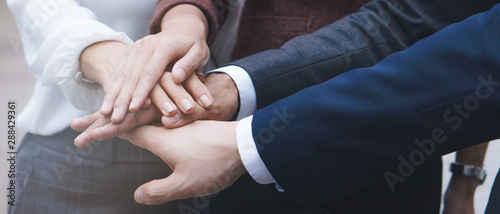 group of business people stacking hands together to cheer up team spirit