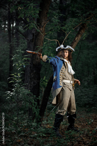 Obraz na plátne 18th-century officer with flintlock gun stands by tree in forest