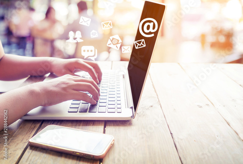 Photo Hand of female using laptop computer sending e-mail message with email address symbol and envelope icon