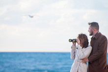 Happy Beautiful Young Couple Fashionable Man And Woman In Autumn Coat Looking Through Binoculars Near Sea With Horizon And Flying Seagull With Copyspace