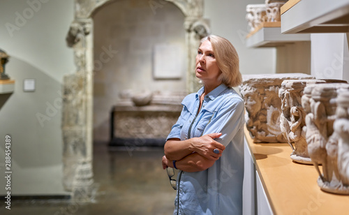 Middle-aged female visitor at the art or archaeological museum. Canvas Print