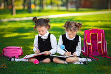 Two Little School Girls With Pink Backpack Sitting On Grass After Lessons And Read Book Or Study Lessons, Thinking Ideas, Education And Learning Concept.