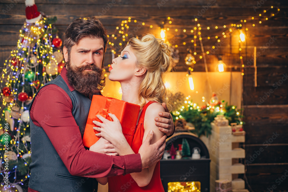 Fototapeta Beautiful Christmas family couple smiling with gift - wish you Happy New Year. Young Christmas fashion couple. Funny couple with colorful make-up and retro hairstyle for Christmas or New Year party.