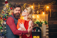 Beautiful Christmas Family Couple Smiling With Gift - Wish You Happy New Year. Young Christmas Fashion Couple. Funny Couple With Colorful Make-up And Retro Hairstyle For Christmas Or New Year Party.
