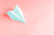 pale blue paper plane on a coral background. trendy 2019 color concept