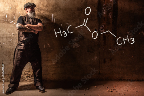 Billede på lærred Bearded old man presenting handdrawn chemical formula of ethyl acetate