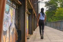 Trendy African Woman Walking Away Across A Bridge