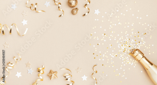 Obraz Champagne bottle with confetti stars, holiday decoration and party streamers on gold festive background. Christmas, birthday or wedding concept. Flat lay. - fototapety do salonu