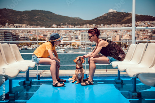 Foto Mother and daughter sitting on the deck of a ferry with a dog